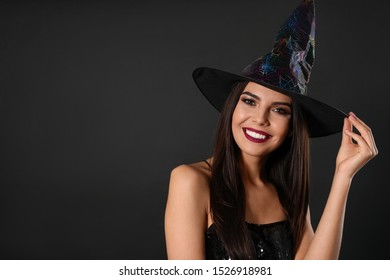 Beautiful woman wearing witch costume for Halloween party on black background, space for text