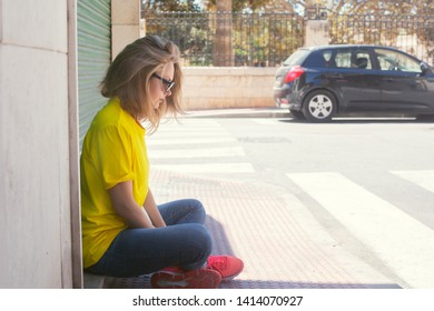 Beautiful woman wears t-shirt, blue jeans and sunglasses sitting on the pedestrian area near city building. She looks sad and pensive. Image contains copy space