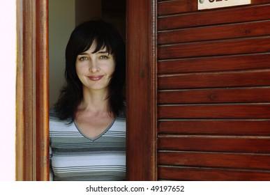 Beautiful woman welcomes at the wooden door
