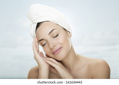 Beautiful woman in wellness with white towel on head