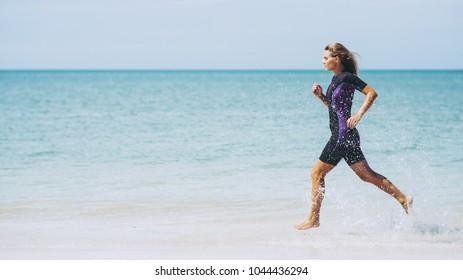 Beautiful woman in wetsuit on the idyllic beach