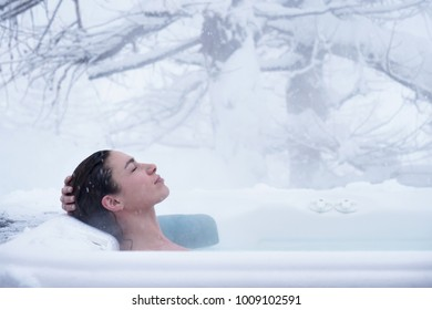 A beautiful woman in the whirlpool relaxes, breathes clean air, and is happy  in the middle of nature as the snow falls from the sky. Concept of: relaxation, nature, wellness.