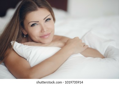 Beautiful woman in white bed. woman lying at bed smiling, with head resting upon her hand