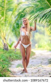 Beautiful woman in white bikini posing between palm trees at the tropical beach. Karon, Phuket, Thailand