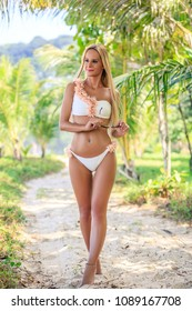 Beautiful woman in white bikini walking between palm trees at the tropical beach. Karon, Phuket, Thailand
