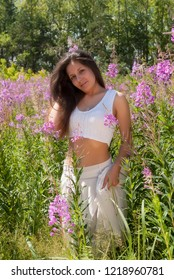 Beautiful woman in white clothes relaxes with bunch of flowers on fireweed meadow