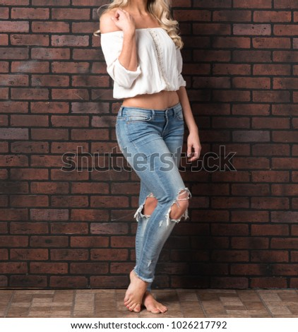 Beautiful Woman In White Crop Top And Distressed Jeans Against A Brick Wall Close Up