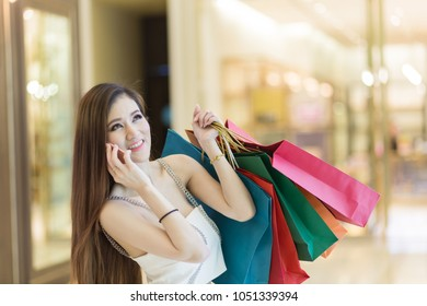 Beautiful Woman in white dress doing online shopping through mobile phone. Girl in fashion look holding colorful bags  in the shopping malls.