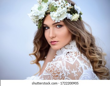 A beautiful woman in a white dress with a flower wreath is sitting near the river. Young girl on the background of a blue forest lake. Close-up soft portrait outdoors