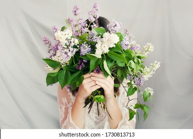 Beautiful woman in white dress hid her face behind large lilac bouquet. Mother's day, Father's day, birthday, eco concept