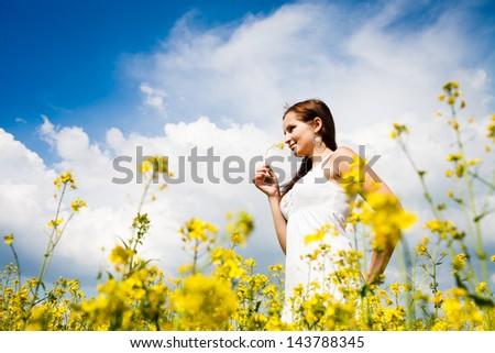 Beautiful Woman in white dress holding a rape flower. Rape Field. Yellow  Field. bf9934fb5