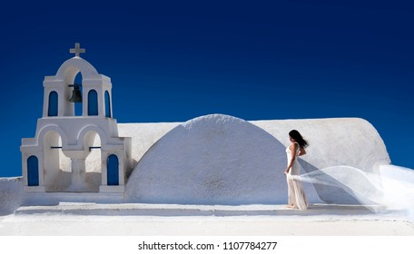 Beautiful woman with a white dress and a scarf in front of a white church