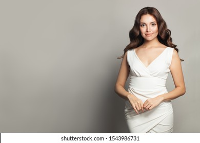 Beautiful woman in white dress standing against gray wall background