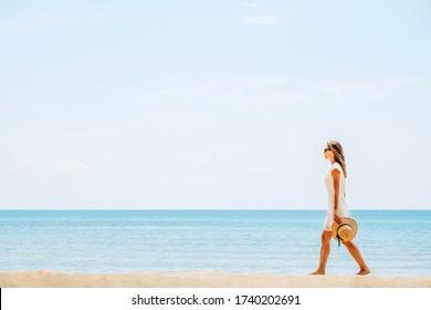 Beautiful woman in a white dress walking on the beach. Breathing fresh air woman near the sea, enjoying summer