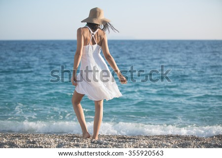 Beautiful woman in a white dress walking on the beach.Relaxed woman breathing fresh air,emotional sensual woman near the sea, enjoying summer.Travel and vacation. Freedom and inspiration concept
