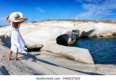 Beautiful woman in white dress walks through the volcanic landscape of Sarakinikowith white chalk rocks against blue sea on the Greek island of Milos