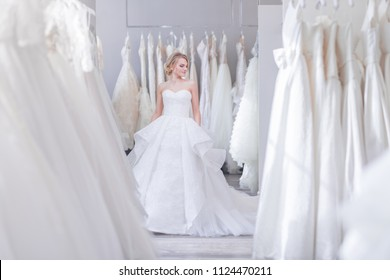 Beautiful woman in a white dress in wedding shop