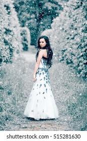 Beautiful woman in white dress in winter park