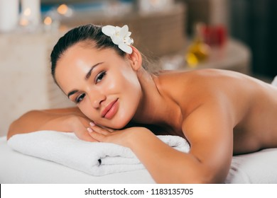 beautiful woman white flower in her hair relaxing at massage salon