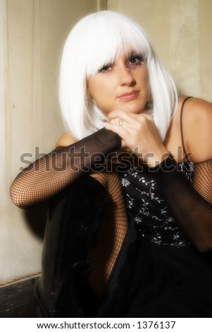 cdad247a680 Beautiful woman with white hair and fishnet formal dress sitting in grunge  room.