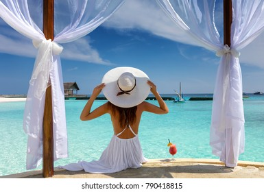 Beautiful woman with white hat enjoys her summer holiday in the tropics