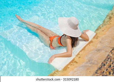 Beautiful woman in white hat lying in a pool.