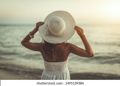 A beautiful woman with white hat on her head is enjoying in sunset on the beach.