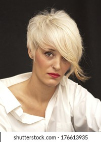 Beautiful woman with white man's shirt and short white hair on black background
