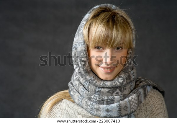 Beautiful woman with a white perfect smile and blue eyes in winter warmly clothed. Portrait of attractive beautiful young woman wearing scarf and winter cap, dark gray background