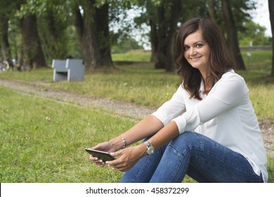 Beautiful woman in white shirt and jeans using tablet in peaceful park