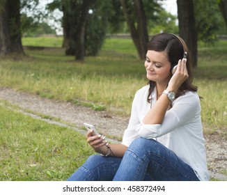 Beautiful woman in white shirt and jeans listening music with headphones in peaceful park