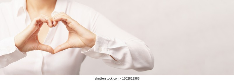 Beautiful woman in white shirt making hands gesture in heart shape showing love, kindness, appreciation and support. Health care, Charity, Organ donation and World heart day concept.