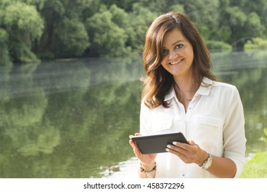 Beautiful woman in white shirt using tablet in peaceful park