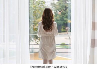Beautiful woman in white silk robe standing near window