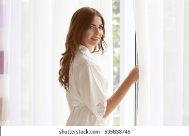 Beautiful woman in white silk robe standing near window