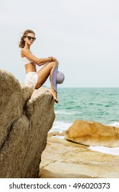 Beautiful woman in white skirt, top and summer straw hat sit on edge of a rock. She look to camera. Beauty cute girl on a tropical beach sea ocean shore with large stones. Outdoor summer lifestyle.