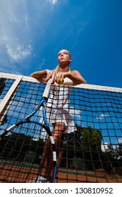 Beautiful woman in a white suit and tennis racket in her hands standing behind the net. Bottom view