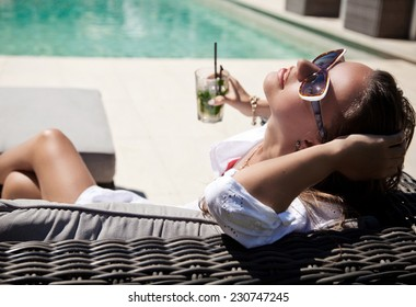 Beautiful woman in white summer dress laying with mojito cocktail on lounge chair at poolside. Luxury vacation