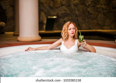 Beautiful woman in white swimsuit sits in whirlpool tube in hydrotherapy spa and drink cocktail mojito