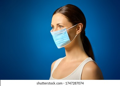 beautiful woman in white t-shirt shows how to wear a mask against a blue background during a pandemic