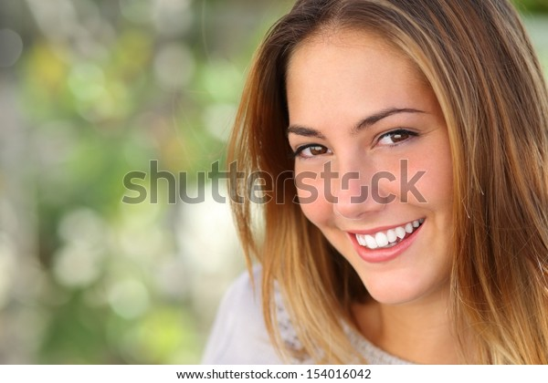 Beautiful woman with a whiten perfect smile outdoor with a green background