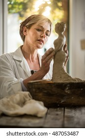 Beautiful woman who makes sculpture with a lap. she is in her atelier. , she is concentrated, she is sculpting a woman . the statue is at foreground. there is a view on garden at background.
