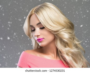 Beautiful woman winter background snowflakes with long blonde beautiful hair