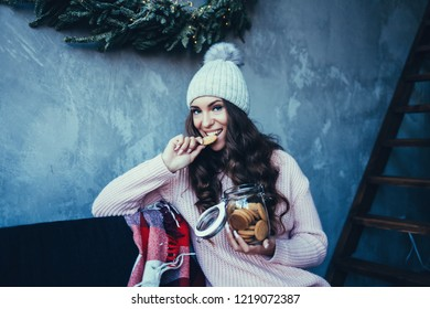 beautiful woman in winter hat eating cookies on new year's eve