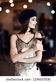 Beautiful woman in winter mink fur hat drinking red wine in expensive restaurant background