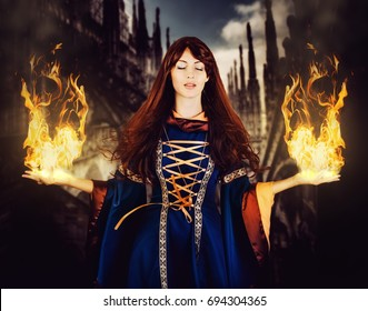 Beautiful woman witch in fantasy medieval dress and long hair. Eyes closed. And hands are divorced in the sides with fire magic. Halloween