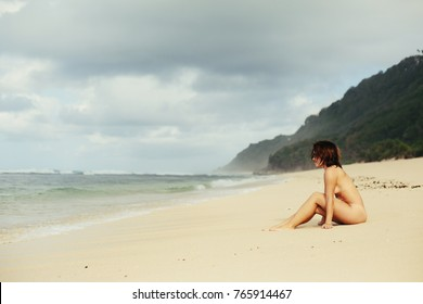 Beautiful woman without swimming suite on ocean shore. Nudist beach