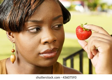 beautiful woman with wooden earrings looks at a strawberry