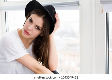 Beautiful woman with a wool hat sitting and daydreaming by the window