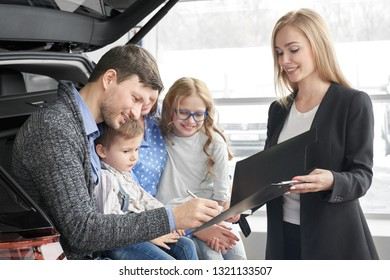 Beautiful woman working as car dealer, holding black folder with document. Man signing contract, purchasing vehicle. Happy family sitting in car trunk, buying new automobile in car dealership.